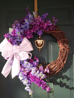 This is a beautiful flower wreath! It measures 23 inches wide, 22 inches long and 6 inches deep. I started out with a grapevine wreath that I added awesome shades of purple Spring flowers too! I also added purple berries and a large white satin bow! This wreath will look great on your