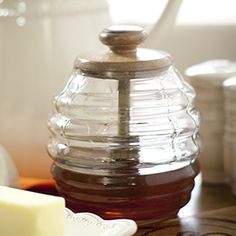 """Product # 16806 Honey Jar 4 1/2"""" tall We know honey is a staple in your household, but the squeeze bottle is a perpetual sticky mess. Keep your honey accessible, neat, and prettily displayed in our Honey Jar. Now there are two options: a honey scoop AND a regular lid. The regular lid option makes the Honey Jar a great option for storing cotton balls, candy, hair barrettes, anything that fits! Mary & Martha is stamped on each lid. Holds approximately 4 cups. Price: $34.00"""