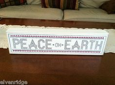 "White wooden box sign. ""Peace on Earth"""