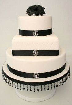 "Black and White Cameo Wedding Cake - 3 tiers with centre quilted effect on fondant, with royal icing piped pearls at the top of the ribbon trim and finished with cameos and a ""corsage"" style camellia on top Black And White Wedding Theme, Black Wedding Cakes, Elegant Wedding Cakes, Cupcakes, Cameo Cake, Royal Icing Piping, Black White Cakes, Wedding Sweets, Black Ribbon"