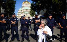 Mulher assopra um apito na frente de uma linha de polícia durante um protesto anti-governo em frente ao Parlamento búlgaro, no centro de Sófia.