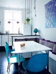 Uma casa em Copenhague de 66 m² aposta no décor em tons de azul e roxo. A sala, conjugada à cozinha, segue com as cores frias que se equilibram nas cadeiras azuis, criadas pelo casal Eames, na tela exposta na parede, nos pendentes próximos à janela e até nas almofadas. A mesa branca é amparada por três cadeiras, mas também por um móvel grande que faz as vezes de sofá.