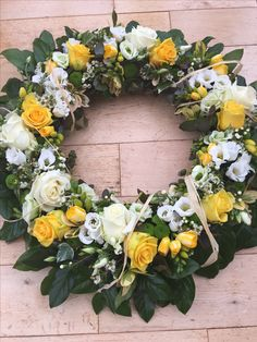 yellow and white sympathy flowers, funeral wreath, country style flowers. Yellow roses, eustoma, freesia and raffia ribbon. Natural country style sympathy flowers.