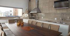 Neste ambiente gourmet com predominância de tons claros, a arquiteta Maximira Durigan projetou e instalou uma grande mesa de madeira de demolição com 3 metros e 14 lugares. Churrasqueira, forno de pizza e a indispensável choperia que os moradores tanto gostam completam a decoração descontraída do local.