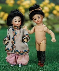 """5"""" Two German All-Bisque Dolls as Asian Children~~~peg-jointed arms and legs, one with painted white stockings and blue slippers, and the other in thigh-high black stockings with brown one-strap shoes.  Marks: 852 2/0 (on one) 3/0 (the other). Comments: Germany, circa 1890. Value Points: rare dolls with fine quality of bisque and painting, unique painted Asian slippers and silk costume on one."""