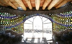 the walls of an earthship home (constructed from tires and mud!)  They are glass bottles in the wall!   I want to live in this!