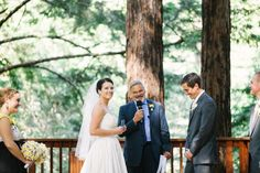 bride jordan, looking at her guests behind the camera, and groom david get married during their beautiful ceremony surrounded by tall redwood trees at their pema osel ling retreat center wedding in the santa cruz redwood mountains in corralitos, ca