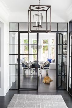 The industrial French doors and Circa Lighting lantern provide a contemporary contrast to the traditionally appointed breakfast area beyond. The family dog relaxes beside a dining table by Big Daddy's Custom, which is surrounded by Made Goods dining chairs.
