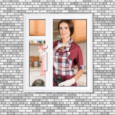 Royalty Free Photo of a Woman Standing by a Window Cleaning