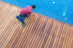 A worker painting exterior wooden pool deck Top view Wooden Pool Deck, Wooden Decks, Deck Flooring, Wide Plank Flooring, Flooring Ideas, Melbourne Architecture, Installing Hardwood Floors, Real Wood Floors, Timber Deck
