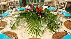 The dining tables at this themed party were decorated with tropical plants and brightly coloured flowers.