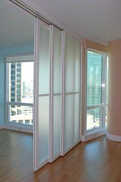 separateur de piece en métal blanc, trois portes coulissantes, espace lumineux, colonne en couleur saumon, sol en parquet PVC marron clair