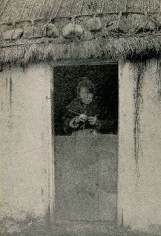 """""""A Knitter in Her Home Doorway"""". Notice the rocks holding the thatch."""