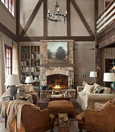 In this cozy Georgia lake house, appealingly asymmetrical built-ins—one with hidden storage, the other open—flank the great room's fieldstone fireplace in the living room.