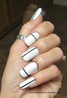 Copy this look by using tape to make thin lines on plain white nails, and use black polish create a simple stripe on each nail. #nails #b&w