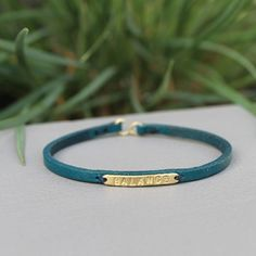 A narrow bar features an inspirational word on a thin leather bracelet. Measurement: Fits up to wrist Materials: Brass with teal: brass and leather Handcrafted Jewelry, Teal, Brass, Bracelets, Leather, Inspirational, Accessories, Handmade Chain Jewelry, Handmade Jewelry