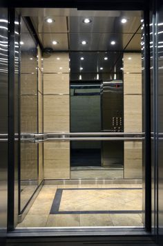 Balfour Building in Toronto Ontario.     Features a custom architectural graphic print behind glass on each side wall. Travertine corner columns brings the lobby materials into the car harmonizing the overall design.