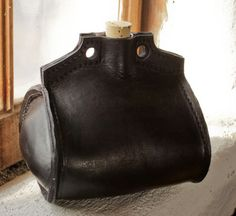 """Also known as a pilgrim bottle, a costrel is a generic term for a tabbed bottle for carrying water, wine, or oil. Surviving examples suggest it was attached to a waistbelt with a short loop strung through the holes and worn on the side of one's hip. These leather bottles are well documented from the 14th century through the 18th century. Handmade by our local leather craftsman. Lined with brewer's pitch. Comes with care instructions. Approx. 6"""" tall by 6"""" long, and holds about 1-1/2 quarts…"""
