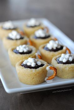 Hot Chocolate Cookie Cups - 1pkg Sugar Cookie Dough 1/2c heavy cream 2TBS hot cocoa mix 1c chocolate chips 1/2c white choc chips 12 mini pretzels 1 c Mallow Bits 1.Put1 TBS dough in mini muffin tin. Bake 12-14 min @ 350. Cool before gently removing Bring chocolate to boil. Stir in cocoa mix.  Pour hot cream over the choc chips let it sit 3 min.stir  Melt white chips and use it to attach the pretzel handles to the cookie cups.  Spoon the chocolate ganache into cups and top with mini…
