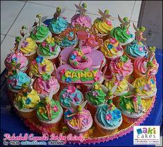 Cupcakes con buttercream colores pastel rosa, amarillo, azul y verde, decorados con florecitas en pastillaje y figuras Campanita en porcelanicrom