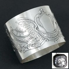 Antique 19th century French sterling silver napkin ring. Decorated in raised relief with Empire style majestic swans with wings outspread. Beautifully