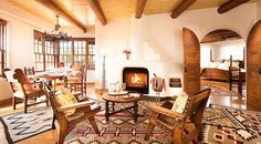 This gorgeous hotel room at the La Fonda Santa Fe features gorgeous textiles, wooden beams, and arched doorways