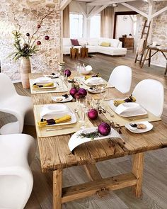 Amazing dining room table, wood floors, stone wall.