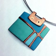 Sapphire Patchwork Pendant by Angela Gerhard. The rectangular shape has a center of copper that has been hand-embossed in a hydraulic press to have an asymmetrical patchwork pattern. It is enameled and fired several times on both sides, and hand-stoned in-between each firing to reveal the raised copper pattern.