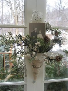 een hoorn met kersttakken en ballen en een foto van een dierbare