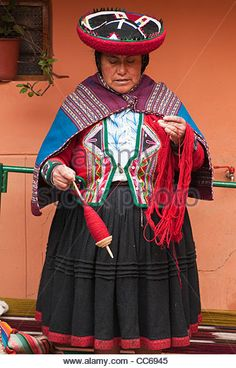 Peru, Chincheros. Peruvian woman in traditional dress spinning wool at the local artisan coop workshop. - Stock Photo