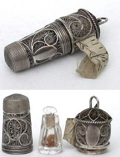 A tall filigree thimble containing a glass scent bottle with a filigree tape measure screwed onto the base.