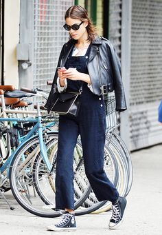 Alexa Chung wears denim overalls with a black leather jacket, a black crossbody bag, black sneakers, and black sunglasses