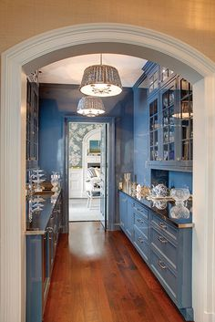 Stainless steel countertops and glass upper cabinets enhance the blue-lacquered walls and cabinetry.