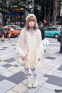 Her romantic look features a layered top an dress with lace and knit, butterfly tights, knit socks and white canvas flats. Her cute cat bag is from Nadia Harajuku.