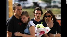 """A couple embraces each other as actor Christian Bale and his wife, Sandra Blazic, wait to place flowers at the memorial across the street from the Century 16 movie theater Tuesday, July 24. Twelve people were killed early Friday during a screening of """"The Dark Knight Rises"""" in Aurora, Colorado. Suspected gunman James E. Holmes was taken into custody shortly after the attack: More photos: Colorado movie theate"""