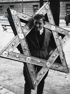A youth carrying the Star of David from the synagogue in Munich following its destruction on Kristallnacht, Munich, Bavaria, 1938 (b/w photo)