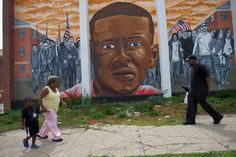 People walk past a mural of Freddie Gray in Baltimore June 23, 2016, after Baltimore Police Officer Caesar Goodson Jr. was found not guilty on all charges regarding Gray's death  while in police custody.