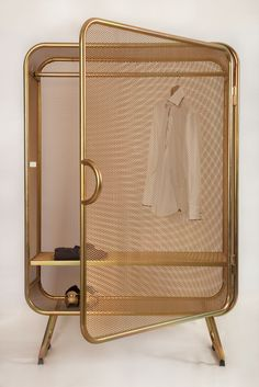 A gold mesh personal cupboard with stylish elements.
