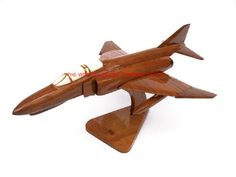 """A beautiful hand carved desktop model of the F-4 Phantom. The model has been carved from solid mahogany. The model comes boxed and is simple to assemble. The wings, tail fins and stand simply slot into pre-drilled holes on the body of the aircraft. No glue required. Size H 7.5"""", L 17"""", W 12"""". Visit our website at http://www.thewoodenmodelcompany.co.uk to view the full range of our models."""