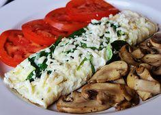 Light Omelette Solo claras relleno de espinacas, queso panela, acompañado de champiñones asados y rebanadas de tomate.