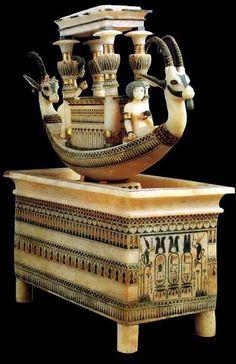Bacile con barca - nuovo regno, XIV secolo a.C. - alabastro scolpito a tutto tondo - dalla tomba di Tutankhamon - museo egizio, Il Cairo. È formato da 2 parti distinte: una barca, ed un recipiente rettangolare che si ipotizza fosse destinato ad essere riempito con petali di fiori. Le decorazioni della barca sono realizzate in foglie d'oro, pietre dure, avorio e pasta vitrea. Quelle del recipiente sono realizzate in oro e pasta vitrea. Nella parte anteriore del bacile sono presenti i cartigli…