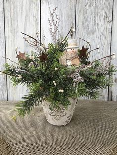 A winter snowman arrangement in a distressed vintage white tin container with pine cones, white pip berries, rusty stars and winter greenery all encasing a snowman figurine that looks like he is sitting in the forest. The centerpiece will look nice on any table, fireplace mantle