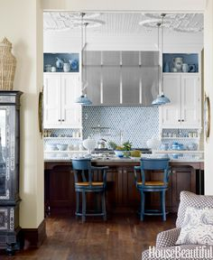 In a Lake Michigan house designed by Martin Horner, the kitchen backsplash, from Urban Archaeology, is beautiful and practical. Open shelves for display break up the cabinetry in the kitchen. Blue mercury-glass pendants from Gallery L7 pick up the color theme. English sabre-leg counter stools from the Sterling Collection.   - HouseBeautiful.com