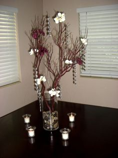 Plum purple and ivory flowers on manzanita branches, planted in natural riverrock.