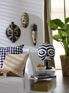African wall masks  These Masks have a fresher, lighter look that many I've seen...I could easily brighten up some of mine...Used with the Plant, they bring much more life to the room than the heavy, dark, that is usually expected from the African Masks...