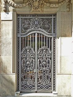 Wrought iron ornamental door on a building on the Passeig de Gràcia in the Eixample district of Barcelona, Catalunya.
