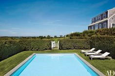 The swimming pool is ringed by a privet hedge; the chaise longues are by Crate and Barrel.