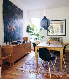 Large art, kilim rug, rustic table with modern chairs