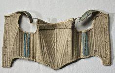 Barnsnörliv, 1700-talet. Linne, valben, järn, sämskskinn.  Ett väl använt snörliv för ett litet barn, av indigoblått linnetyg kantat med skinn. Foder av oblekt linnekypert. Insydda styvnader av valben sitter tätt, över bröstet en välvd järnskena. Axelbanden regleras med sämskskinnsband som knyts fram. Snörning i ryggen med hål och snörbandav vitt linne. I nederkanten två mässingsöglor.