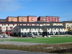 A soccer field with artificial turf is surrounded by apartment buildings in the Nuussuaq district of Nuuk, Greenland. Nuuk Greenland, Greenland Travel, Tours, Artificial Turf, Mansions, Country, House Styles, City, Claire